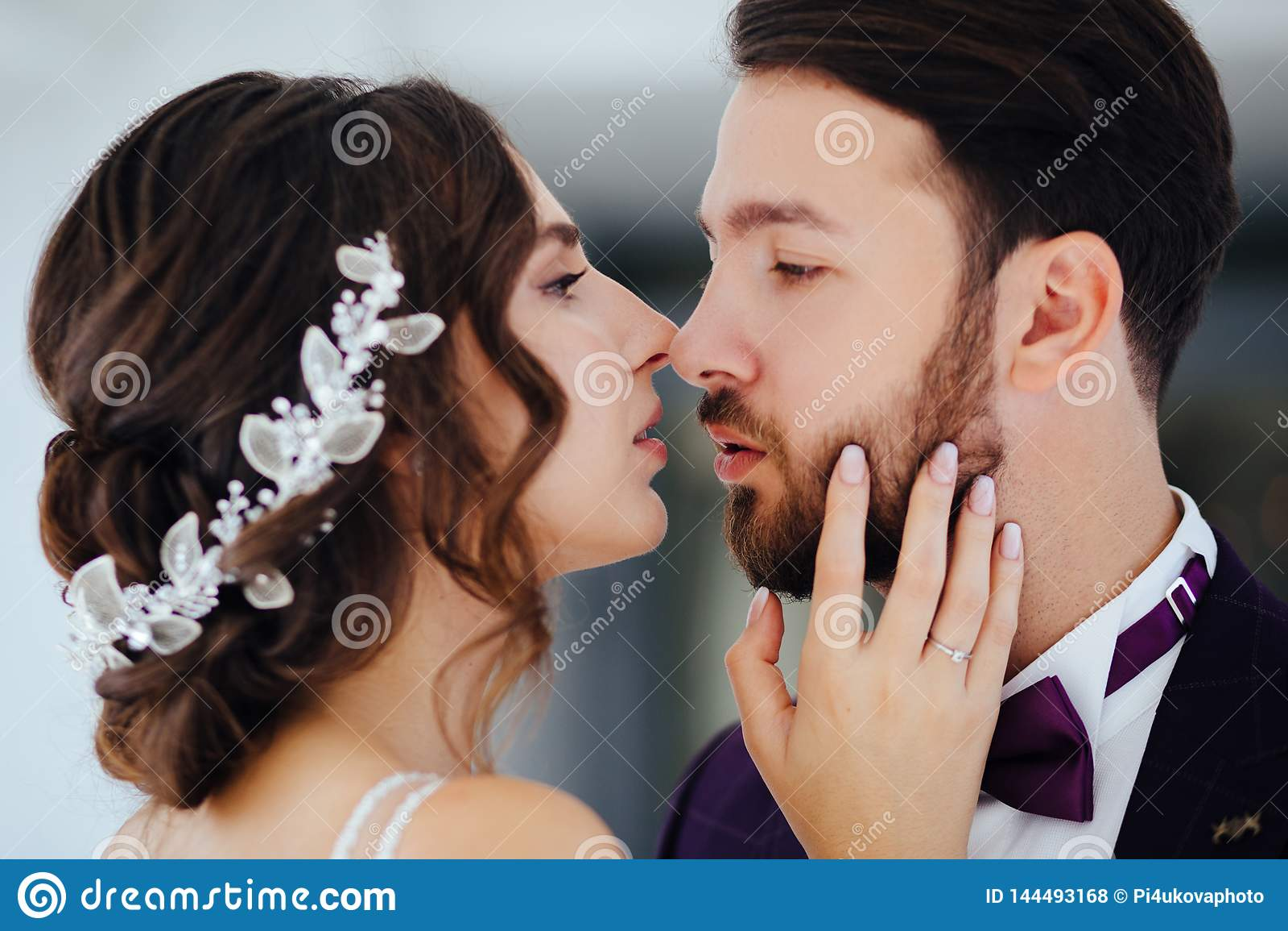 De en bruid en bruidegom die koesteren de kussen newlyweds