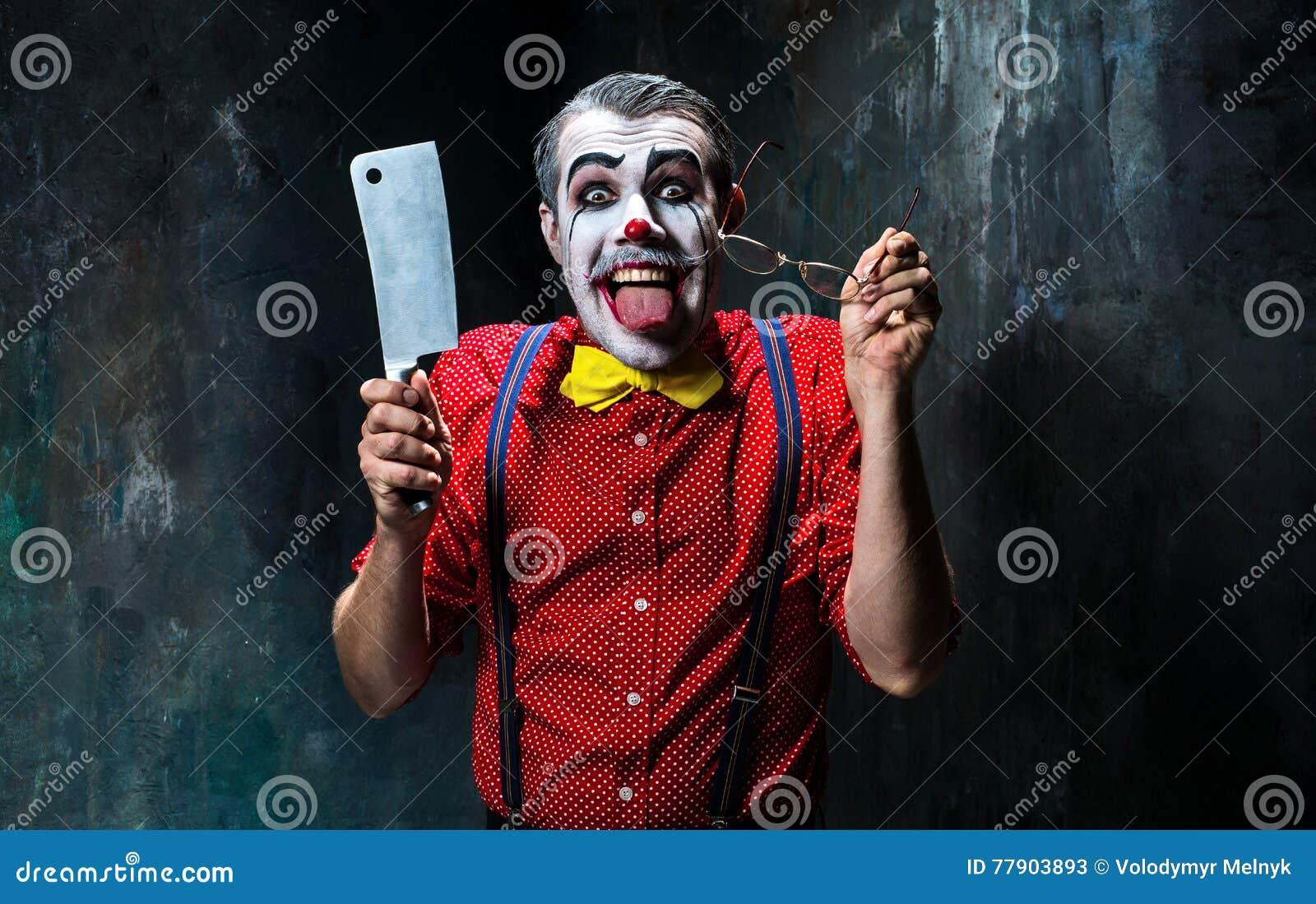 De enge clown die een mes op dack houden Het concept van Halloween
