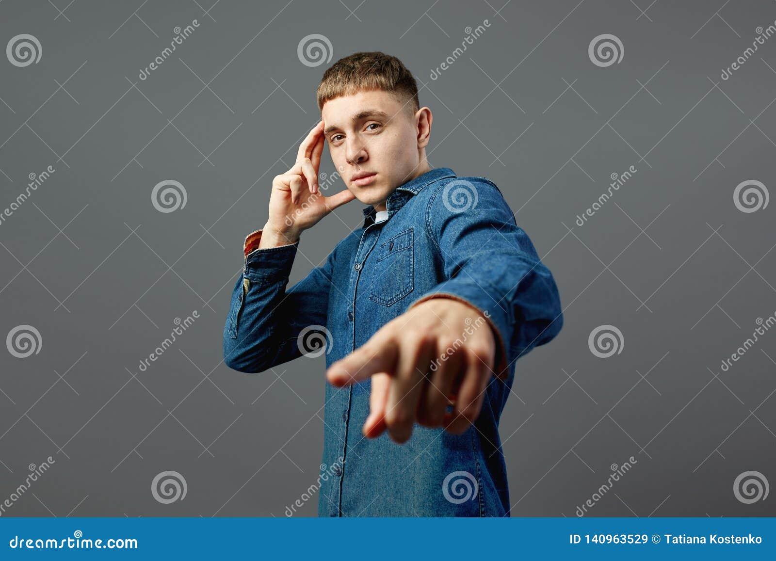 De ernstige kerel kleedde zich in een jeansoverhemd die zich met zijn hand op zijn gezicht bevinden en richt vooruit de andere ha