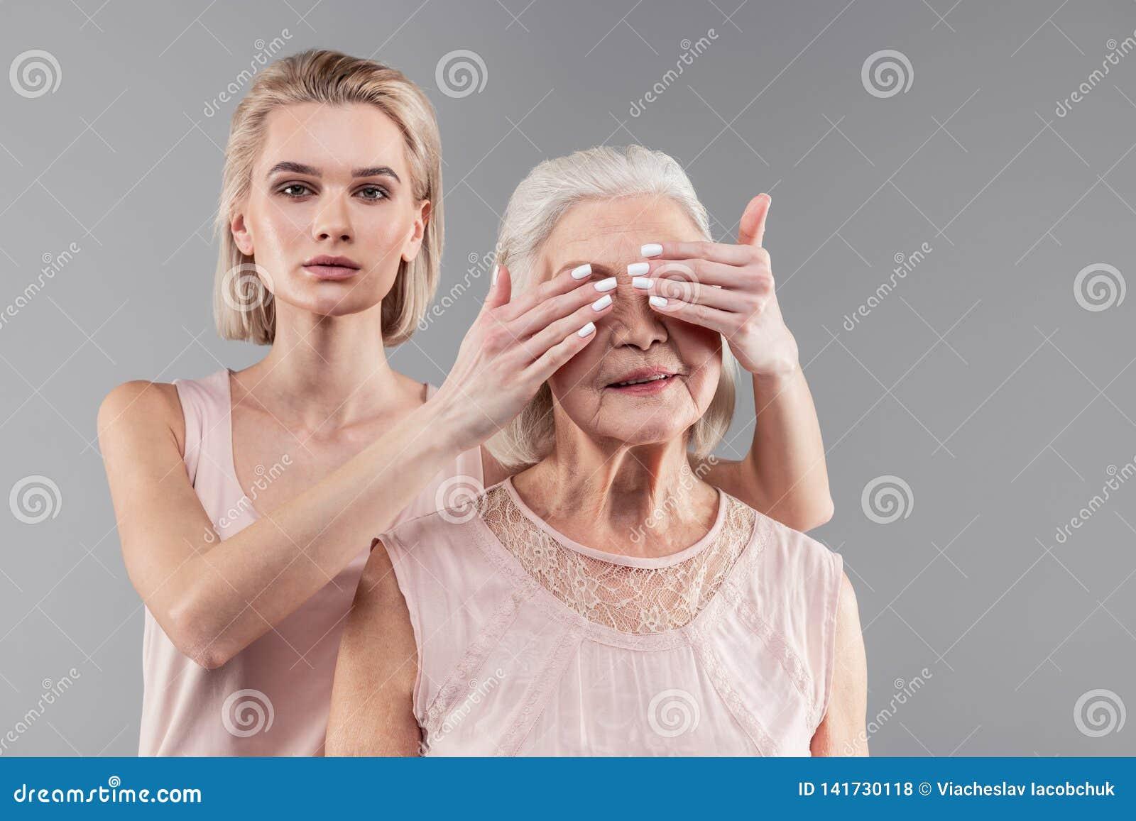 De ernstige sluitende ogen van het kortharige blondemeisje van haar hogere moeder