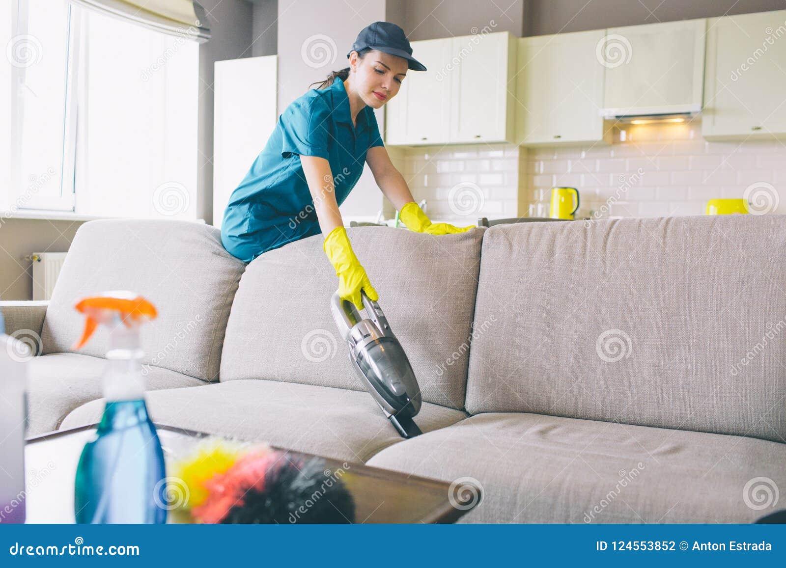 De ernstige vrouw bevindt zich en leunt aan bank Zij werkt met kleine stofzuiger Het meisje draagt eenvormig en handschoenen