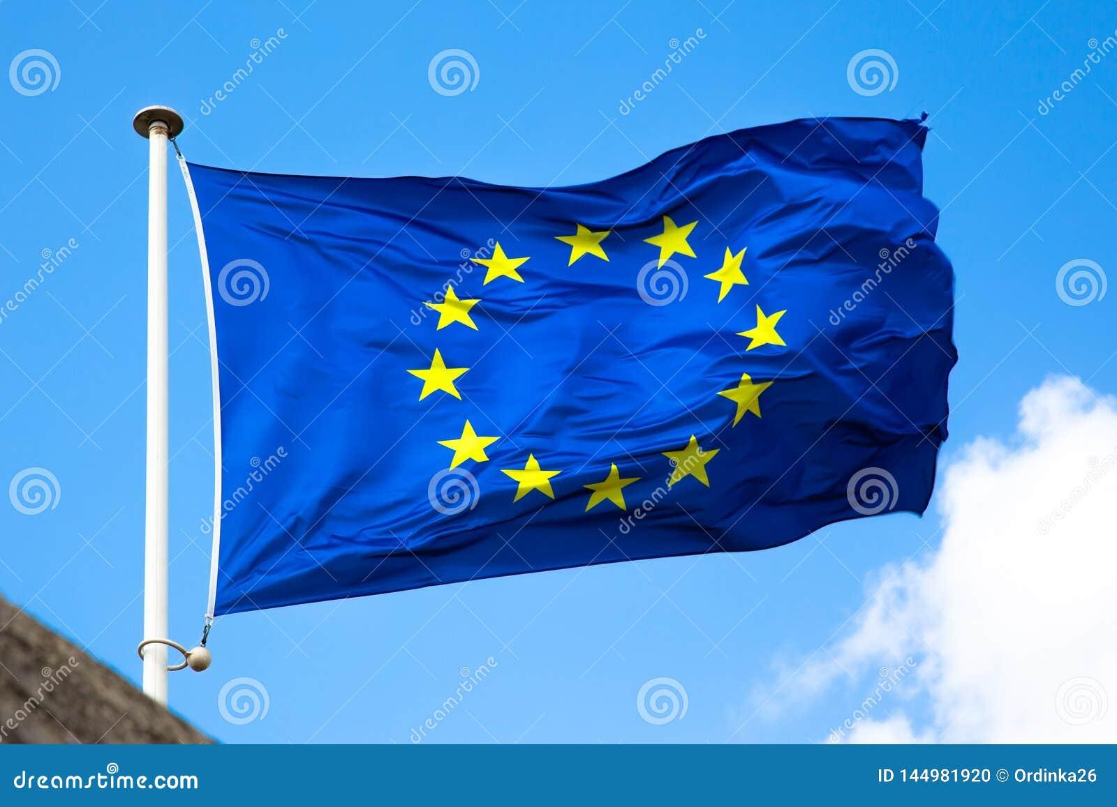 De EU-vlagclose-up op blauwe hemel als achtergrond
