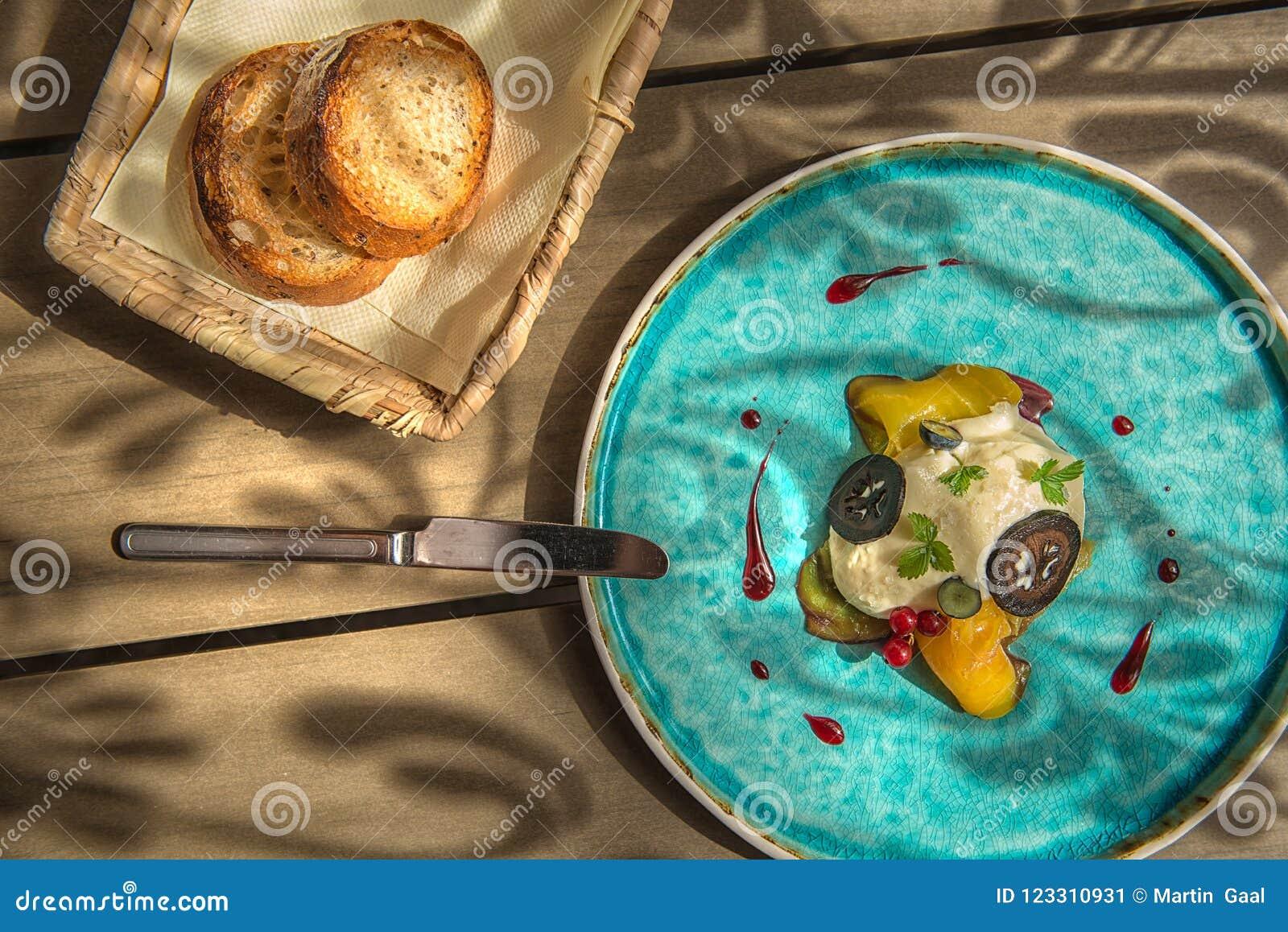 De exclusieve kaasmousse met gemarineerde okkernoten en gouden bieten diende op turkooise plaat, hoogste gastronomie