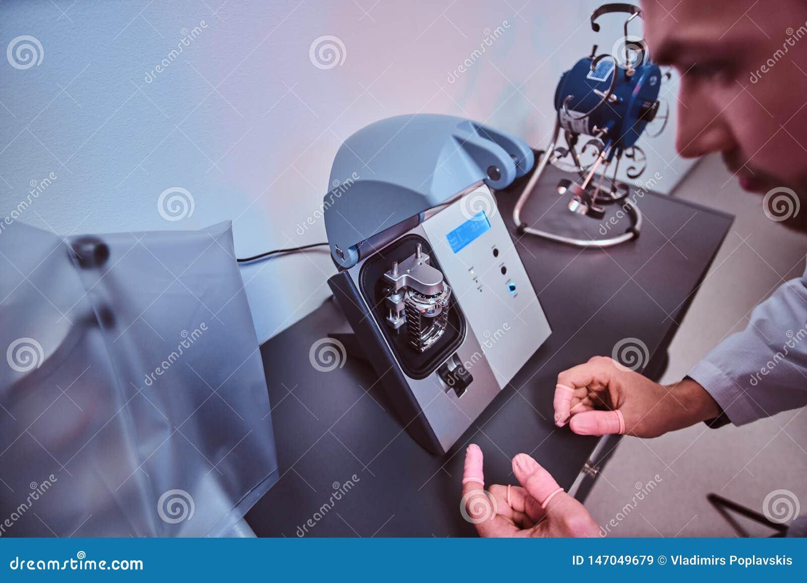 De Expiriencedhorlogemaker doet gravure voor het horloge van custmer gebruikend speciaal hulpmiddel op zijn workshop