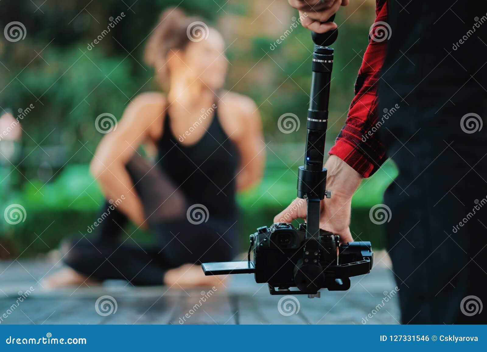 De exploitant die van de videocameramens met beroepsuitrusting werken, die opname filmen Cameraman die video van yoga schieten