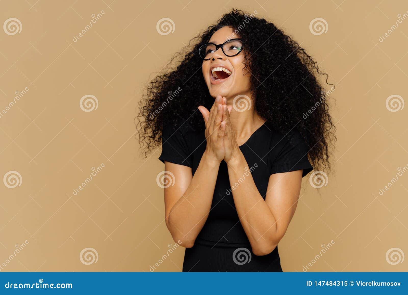 De extatische mooie vrouwengrepen overhandigt vreugdevol, lacht, weg kijkt, opzij geconcentreerd, uitdrukt geluk, heeft dichtbegr