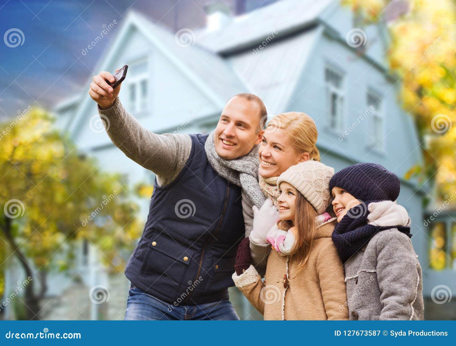 De familie neemt de herfst selfie door cellphone over huis