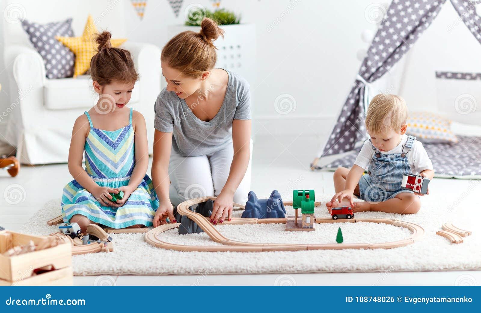 De de familiemoeder en kinderen spelen een stuk speelgoed spoorweg in speelkamer