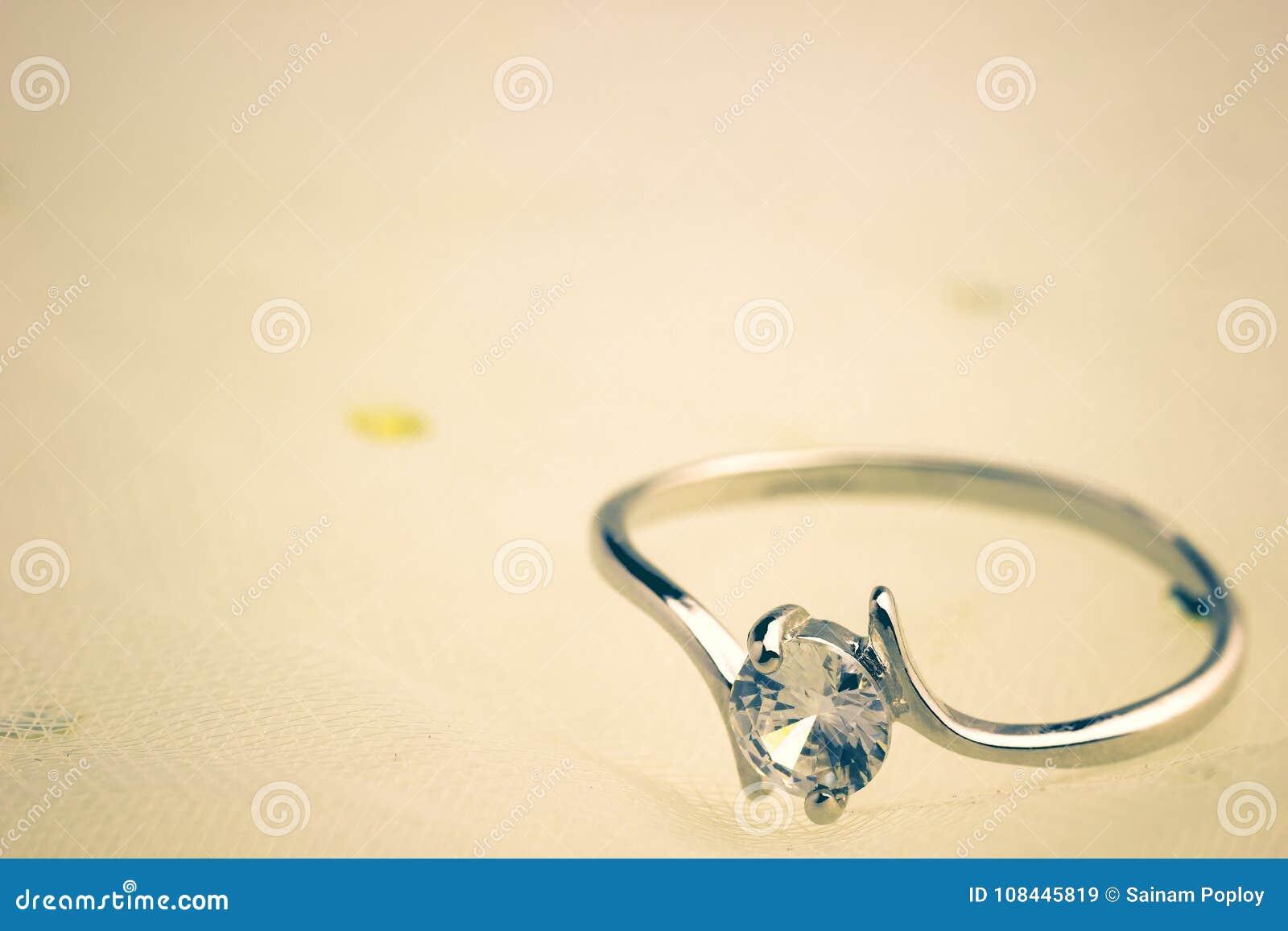 De fausses bagues à diamant sont placées sur une robe de mariage blanche