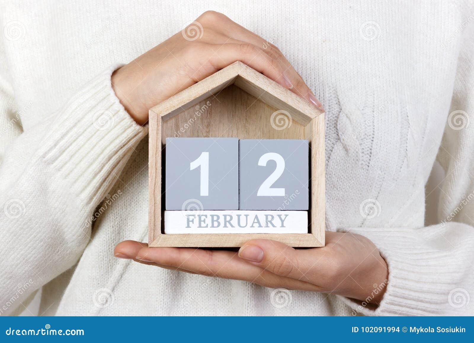 12 de febrero en el calendario la muchacha está sosteniendo un calendario de madera Día internacional de agencias de la boda, día