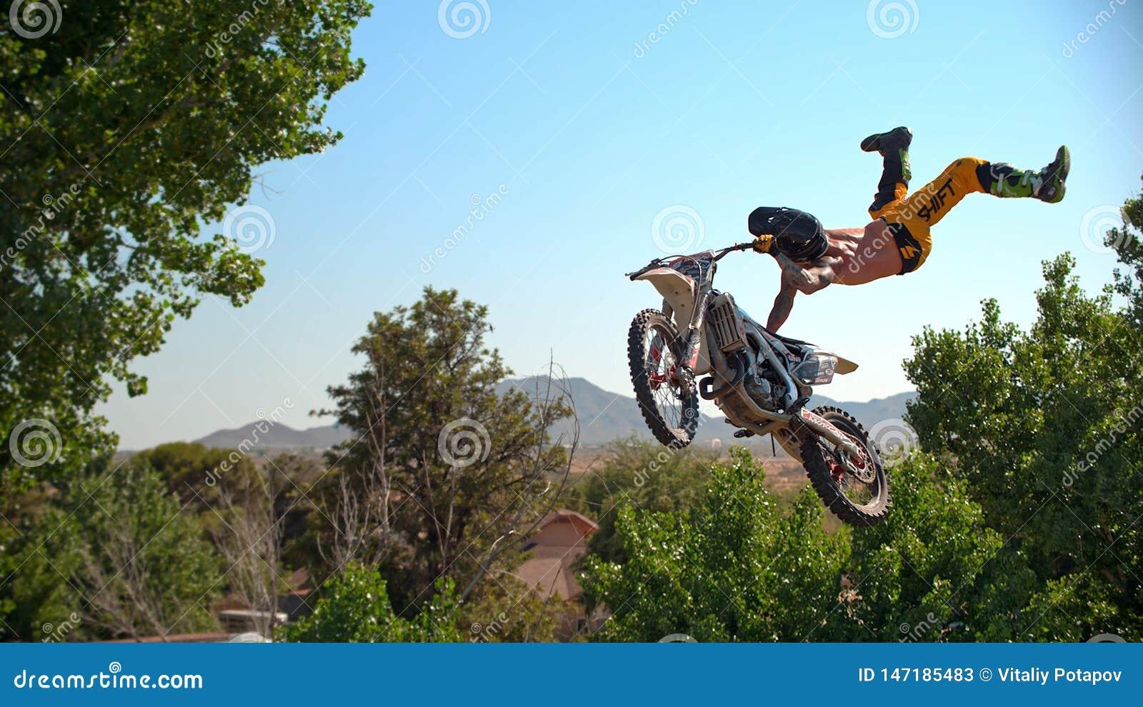 De fietser van de vrij slagmotocross voert de truc in sprong bij fmxcompetities uit