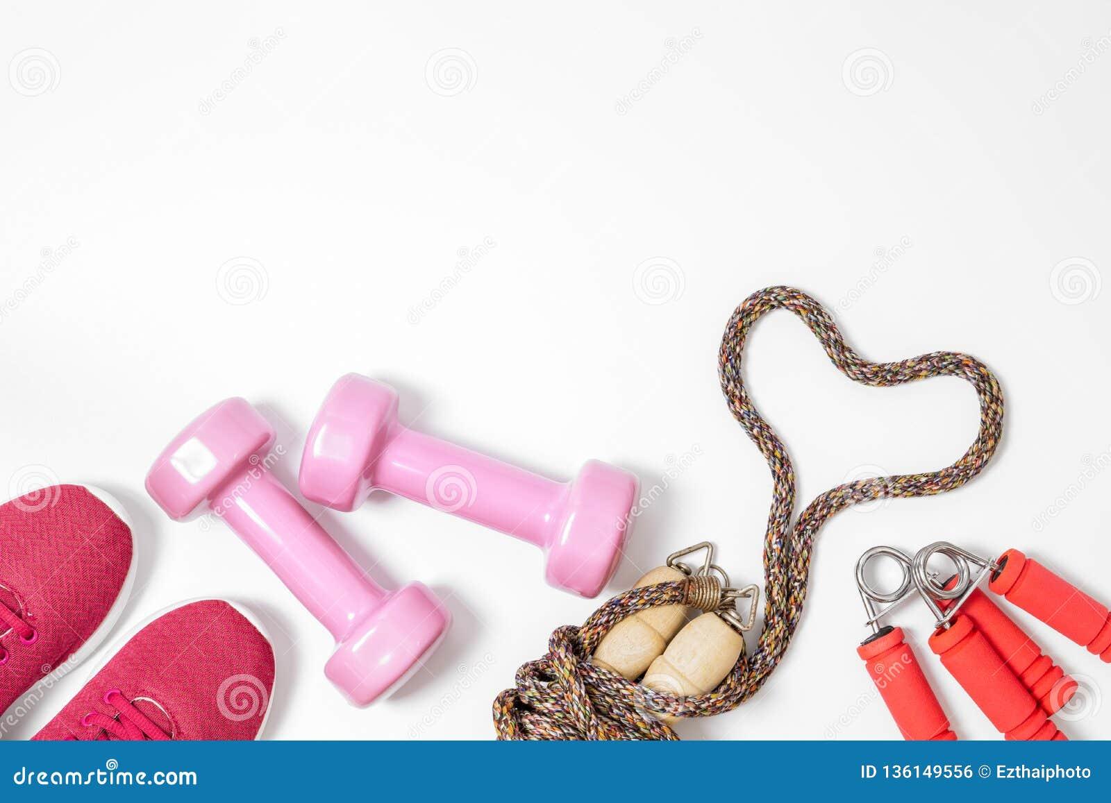 De fitness, gezonde en actieve levensstijlen houden van concept, domoren, sportschoenen en springtouw in hartvorm op witte achter
