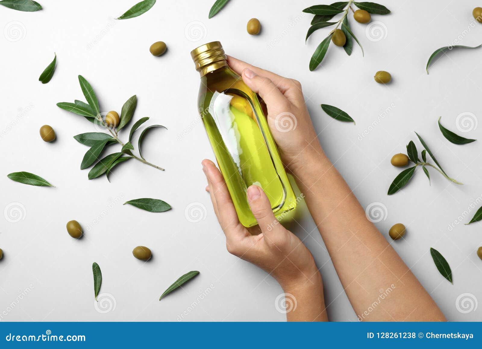 De fles van de vrouwenholding olijfolie op lichte achtergrond