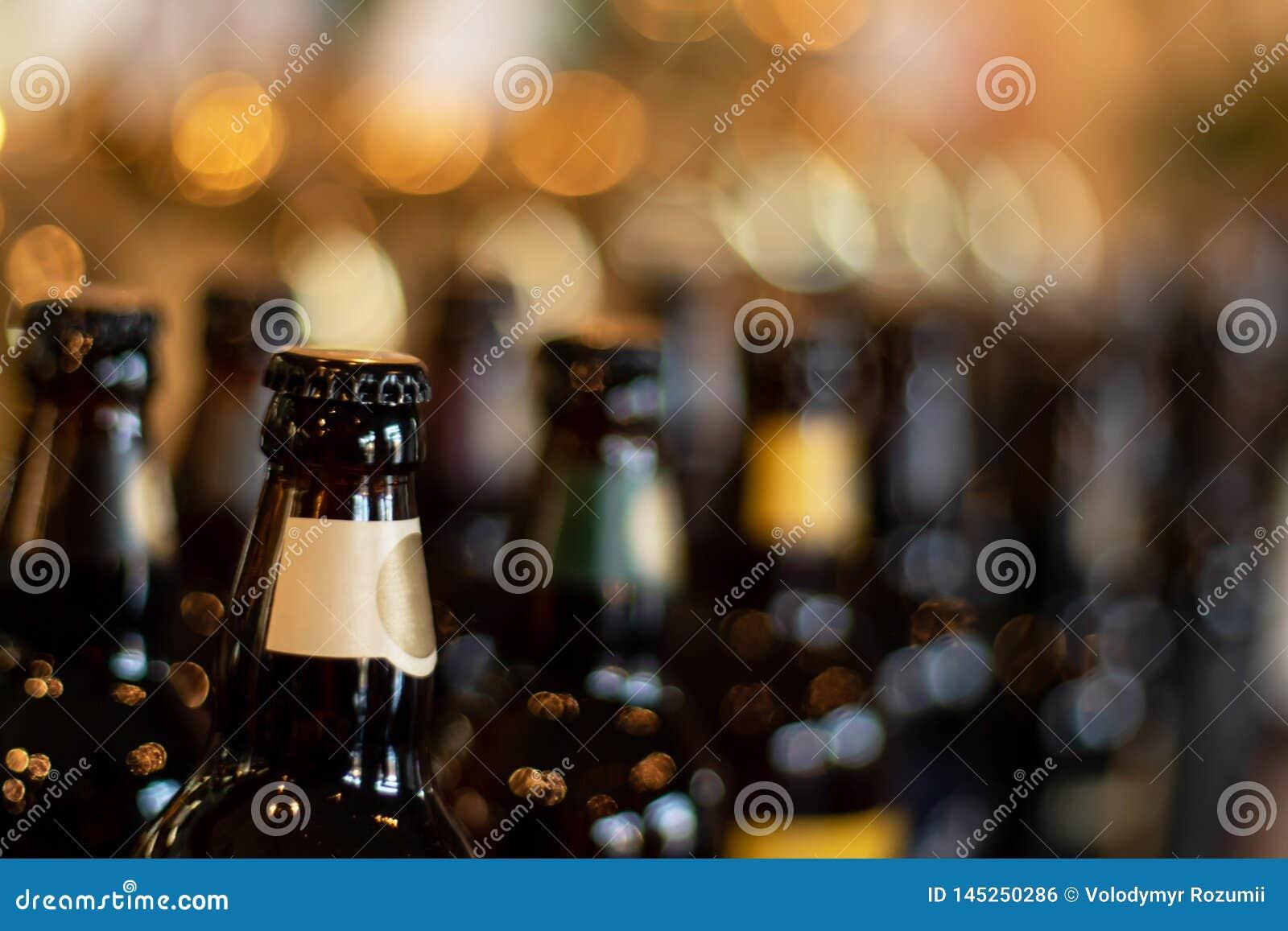 De flessen bier bevinden zich op de achtergrond van de onduidelijk beeldbar in de avond