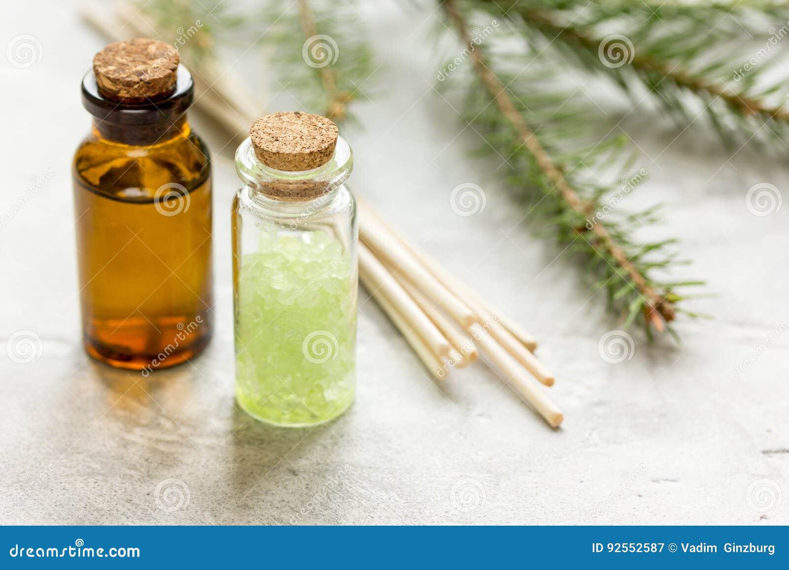 De flessen etherische olie en spar vertakt zich voor aromatherapy en kuuroord op witte lijstachtergrond