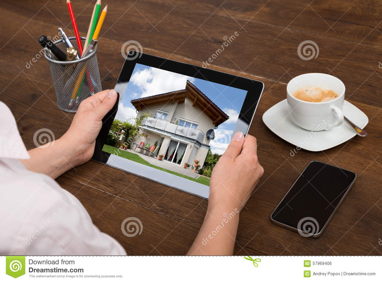 De Foto van Businesspersonlooking at house op Digitale Tablet