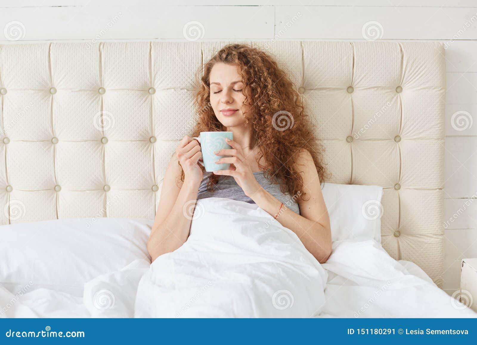 De foto van het charmeren van jonge vrouw met krullend haar, die in bed, het drinken aromatische koffie ii zijn ochtend, kijkt ka