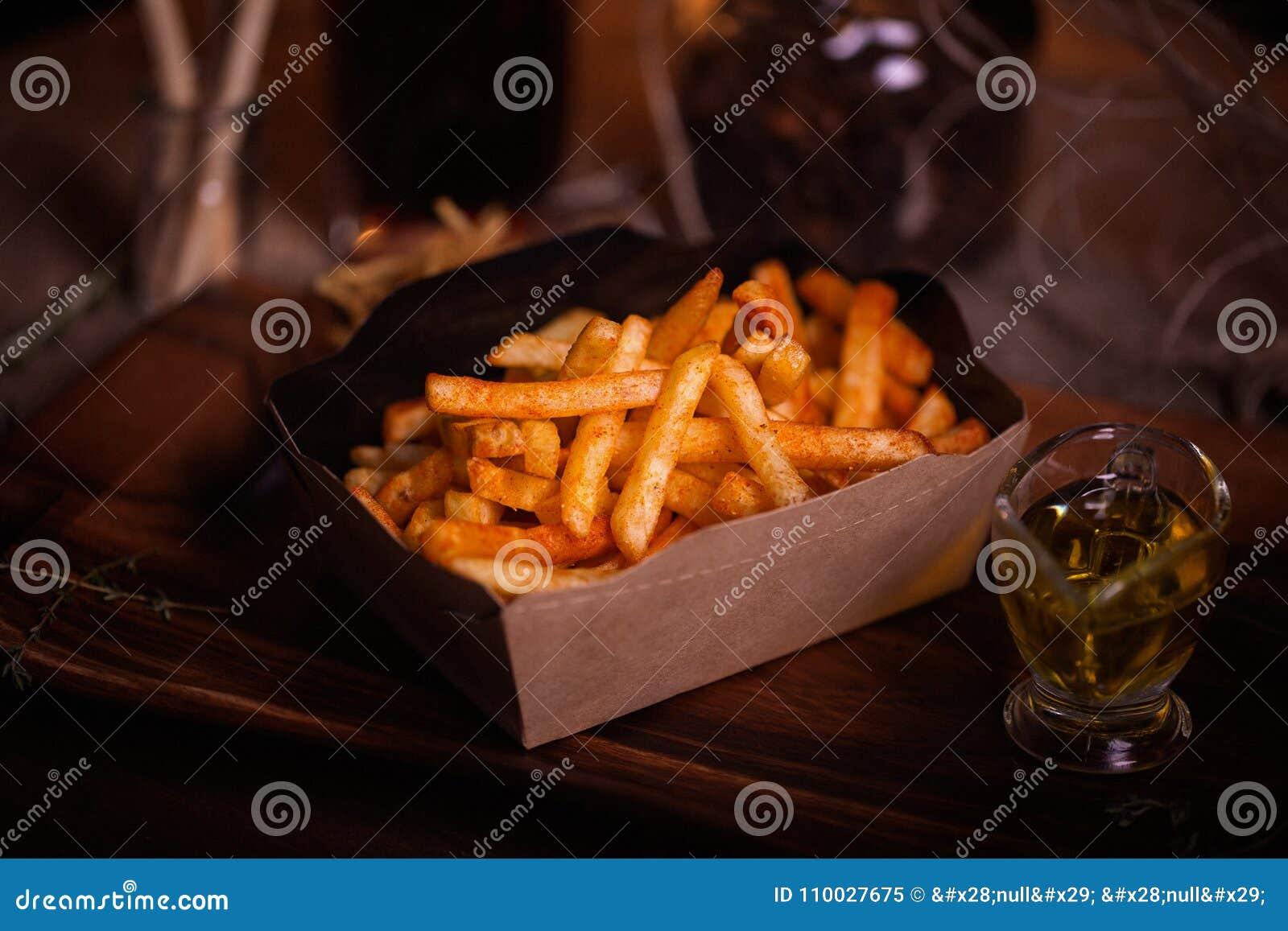 De foto van het gebraden gerechtenvoedsel Straatvoedsel Ongezonde smakelijke geroosterde frieten in eigengemaakte ambachtdoos De