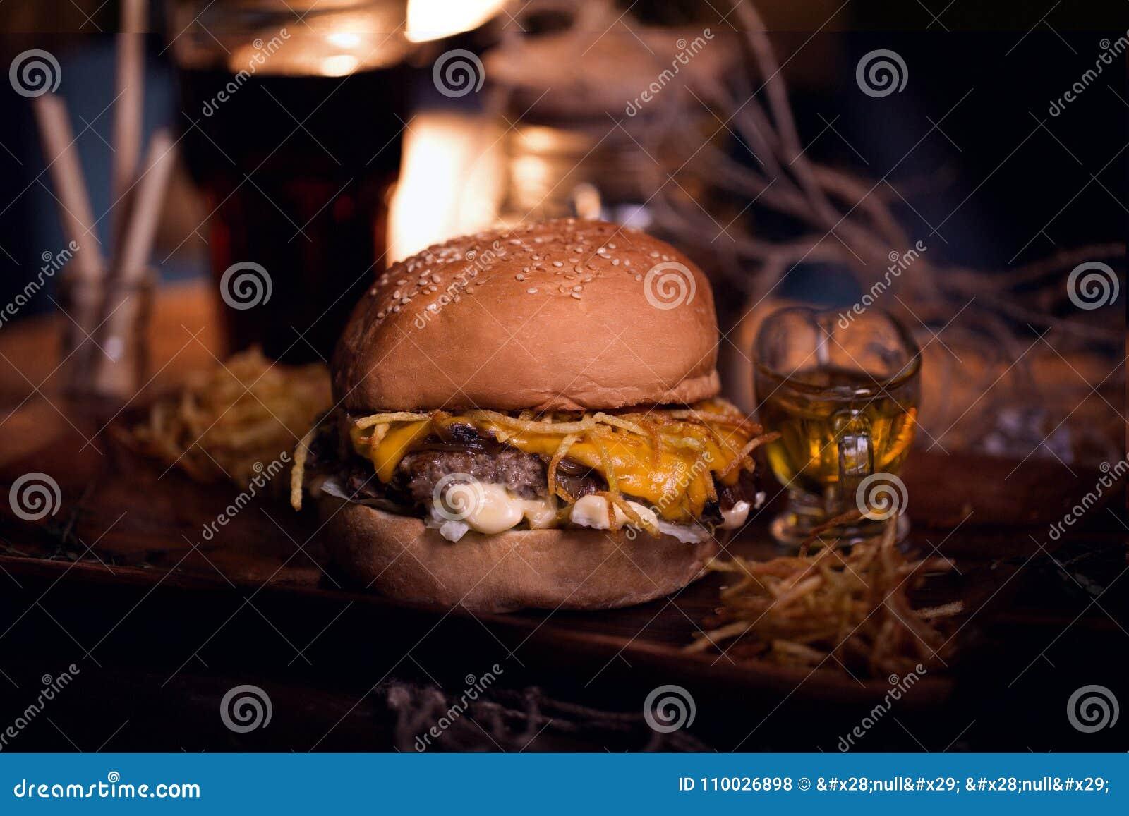 De foto van het hamburgervoedsel Straatvoedsel Verse smakelijke geroosterde die rundvleeshamburger bij barbecue op houten lijst w