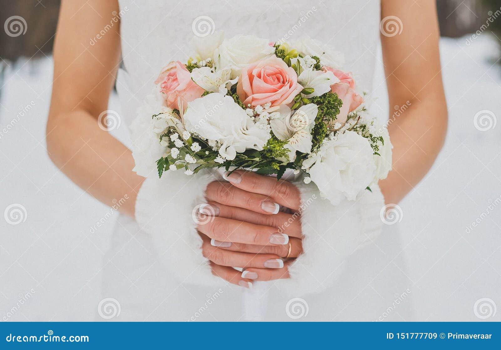 De foto van het de winterhuwelijk bruids boeket in de handen van de bruid Close-up Boeket van Roze Rozen