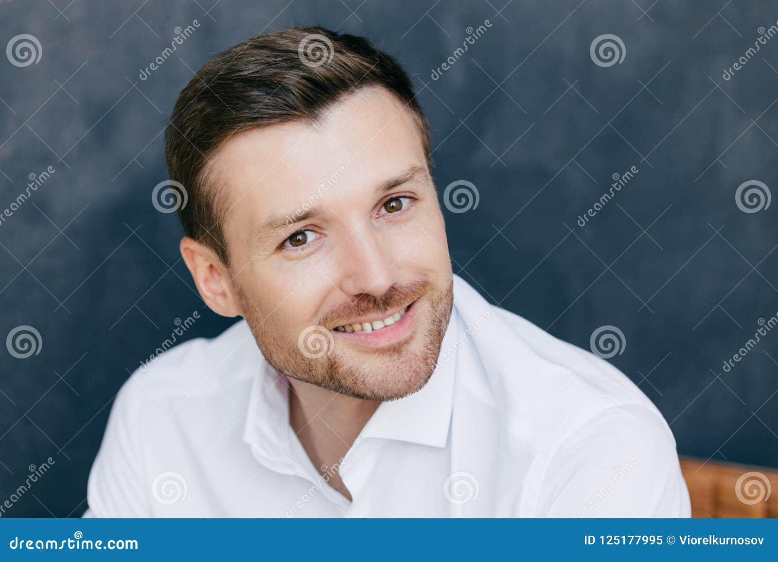 De foto van knap ongeschoren mannetje met varkenshaar gekleed in elegant wit overhemd, heeft charmante glimlach, gelukkig om oude