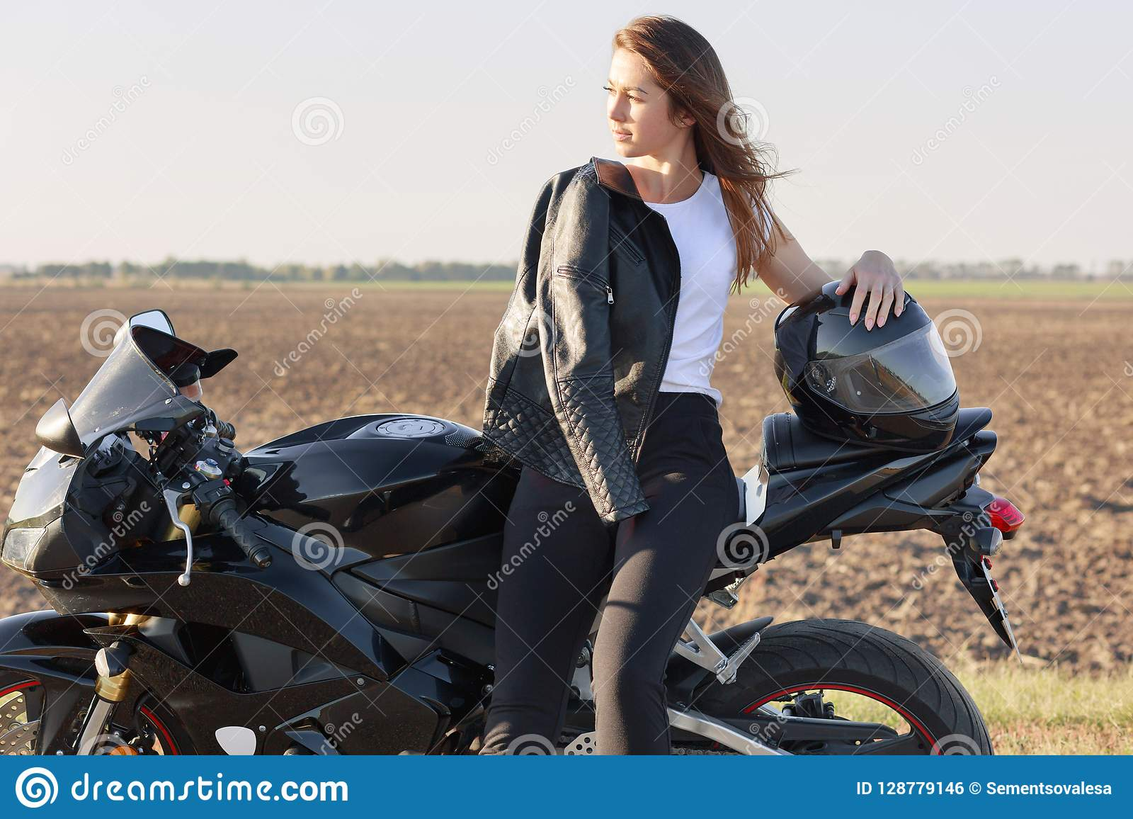 De foto van nadenkend Kaukasisch wijfje houdt van berijdend motor, stelt dichtbij haar snelle fiets, heeft leerjasje op schouder,