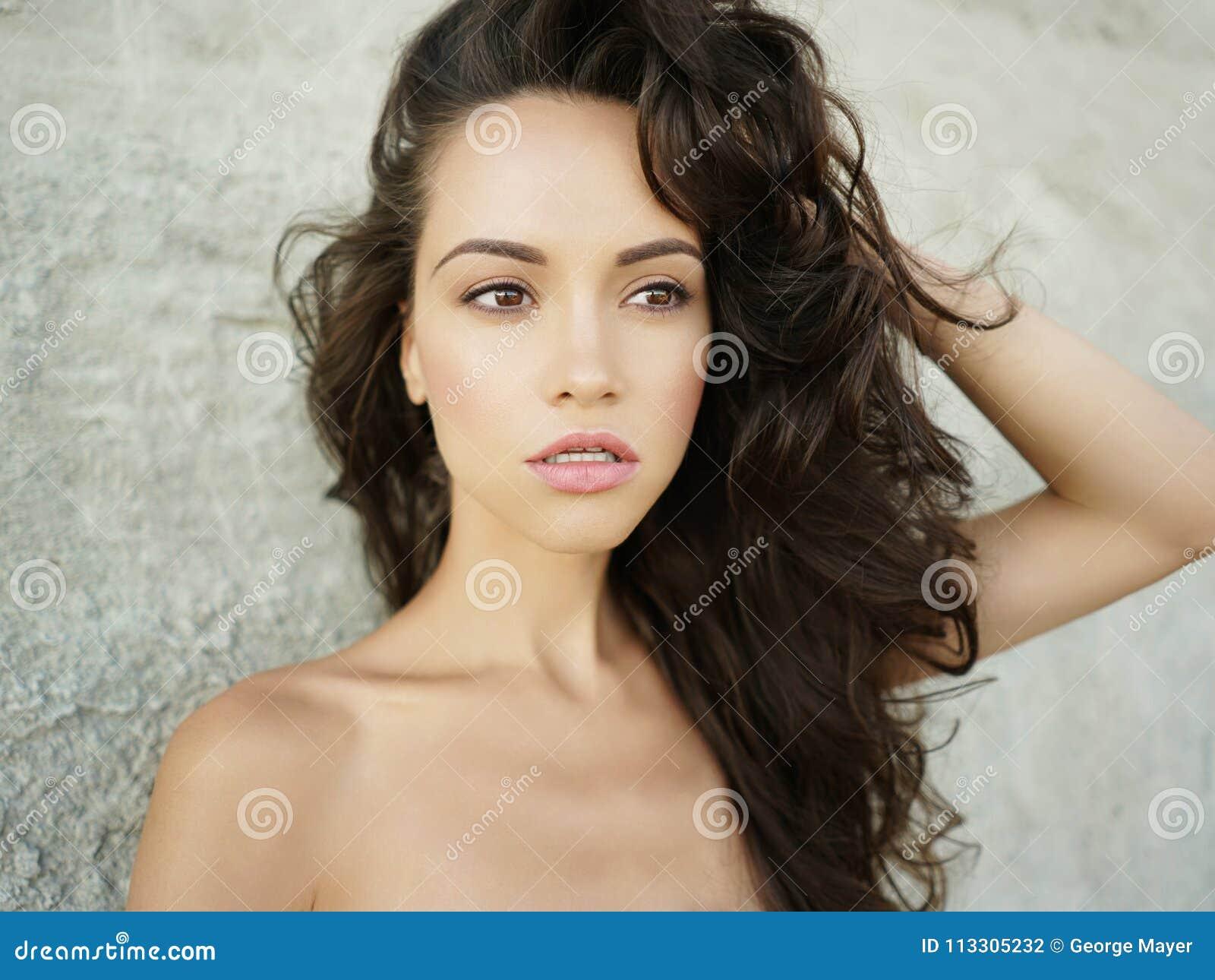 De foto van de voorraad van mooie lange donkerbruine vrouw op het strand in