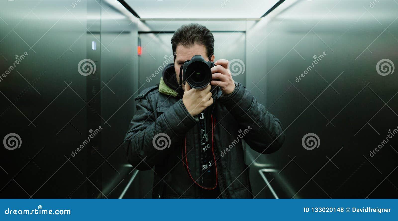 De fotograaf die een cinematic spiegel selfie met analoge wolframfilm nemen kijkt en korrel voor ISO 800