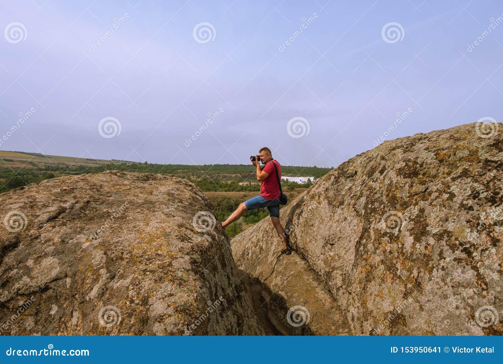 De fotograaf neemt beelden van aard, die zich bovenop een klip bevinden