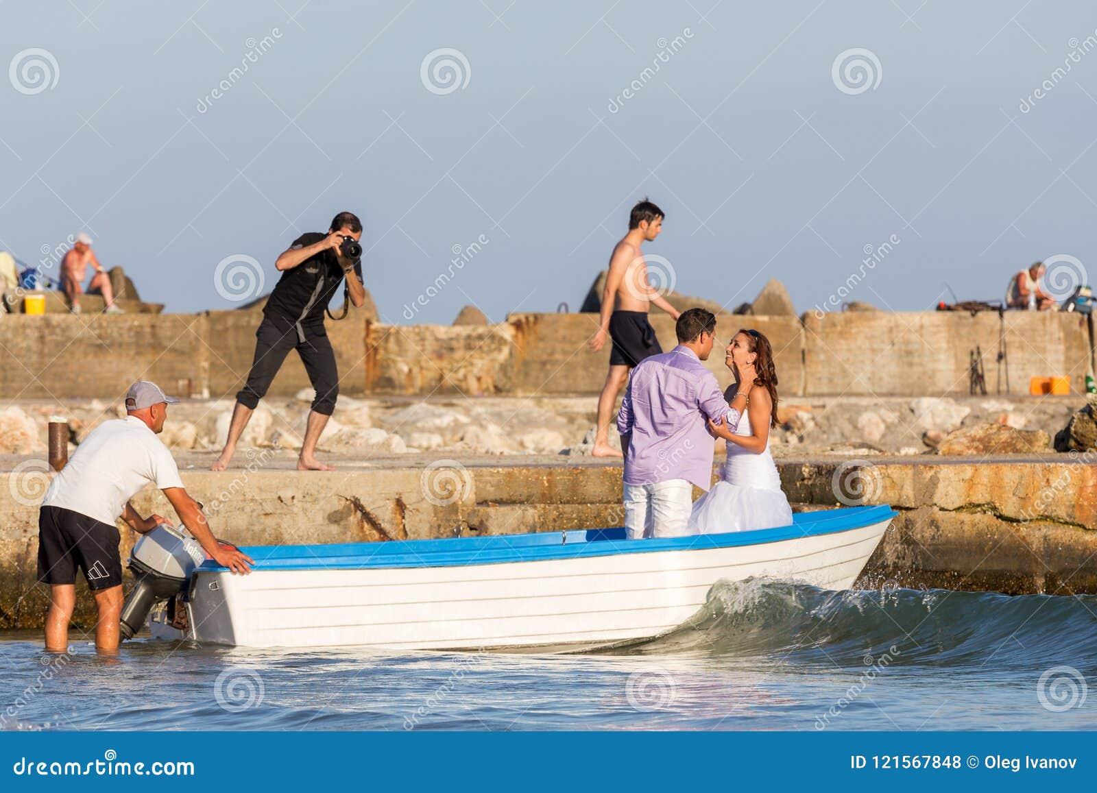 De fotograaf schiet een paar hartelijke jonggehuwden in een boot in de baai van de Zwarte Zee
