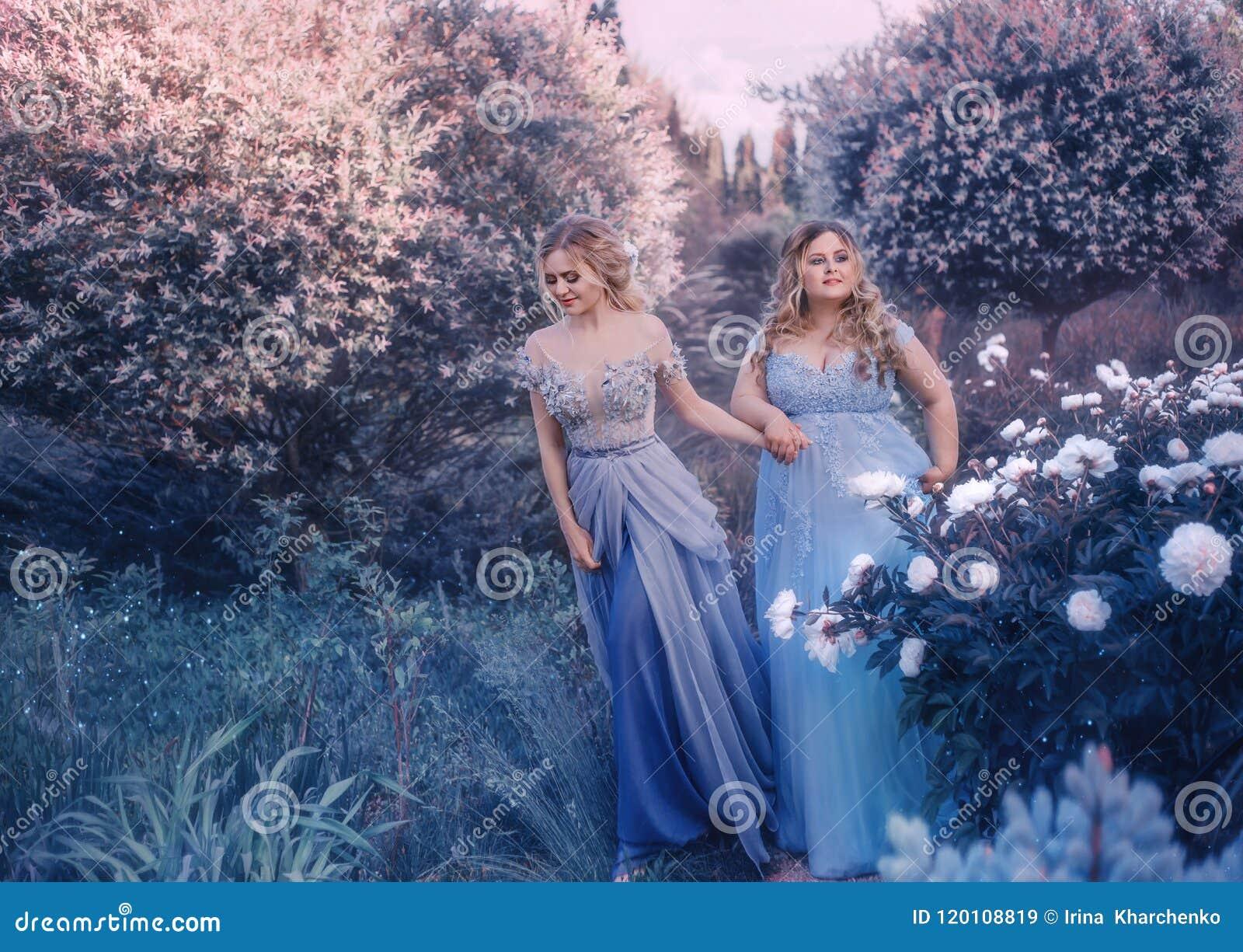 De fotospruit van de familiefee Twee blonde vrouwen met golvend haar in luxueus, fabelachtig, blauw kleedt zich tegen de achtergr