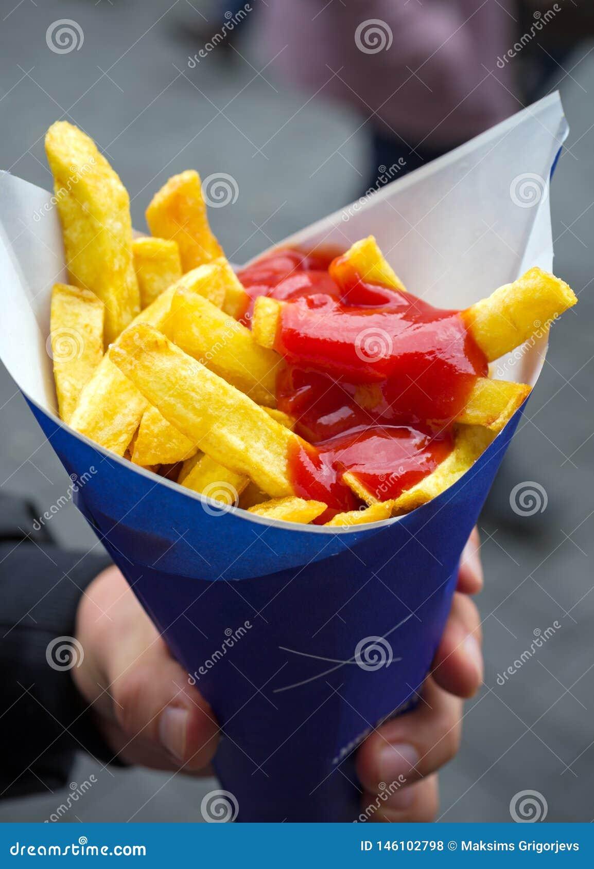 De Frieten van de mensenholding in document kornet met ketchup Straatvoedsel