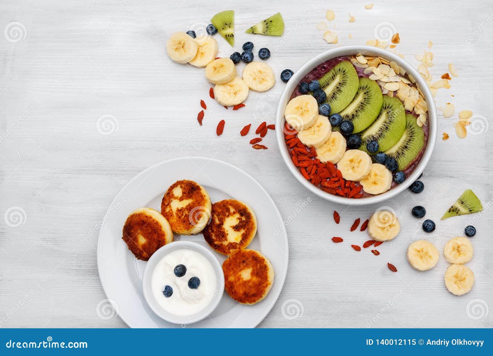 De fruitmousse in kommen voor gezonde ontbijt Verse organische smoothie maakte van banaan, kiwi, spirulina, wheatgrass en
