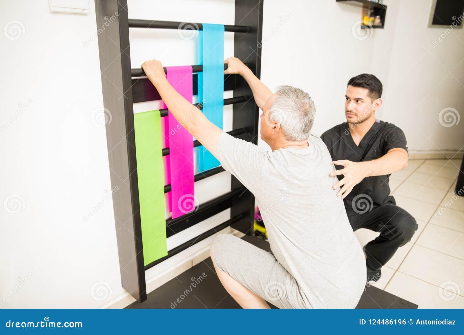 De fysiotherapeut Looking At Wall verspert terwijl het Bijstaan van Geduldige Doi