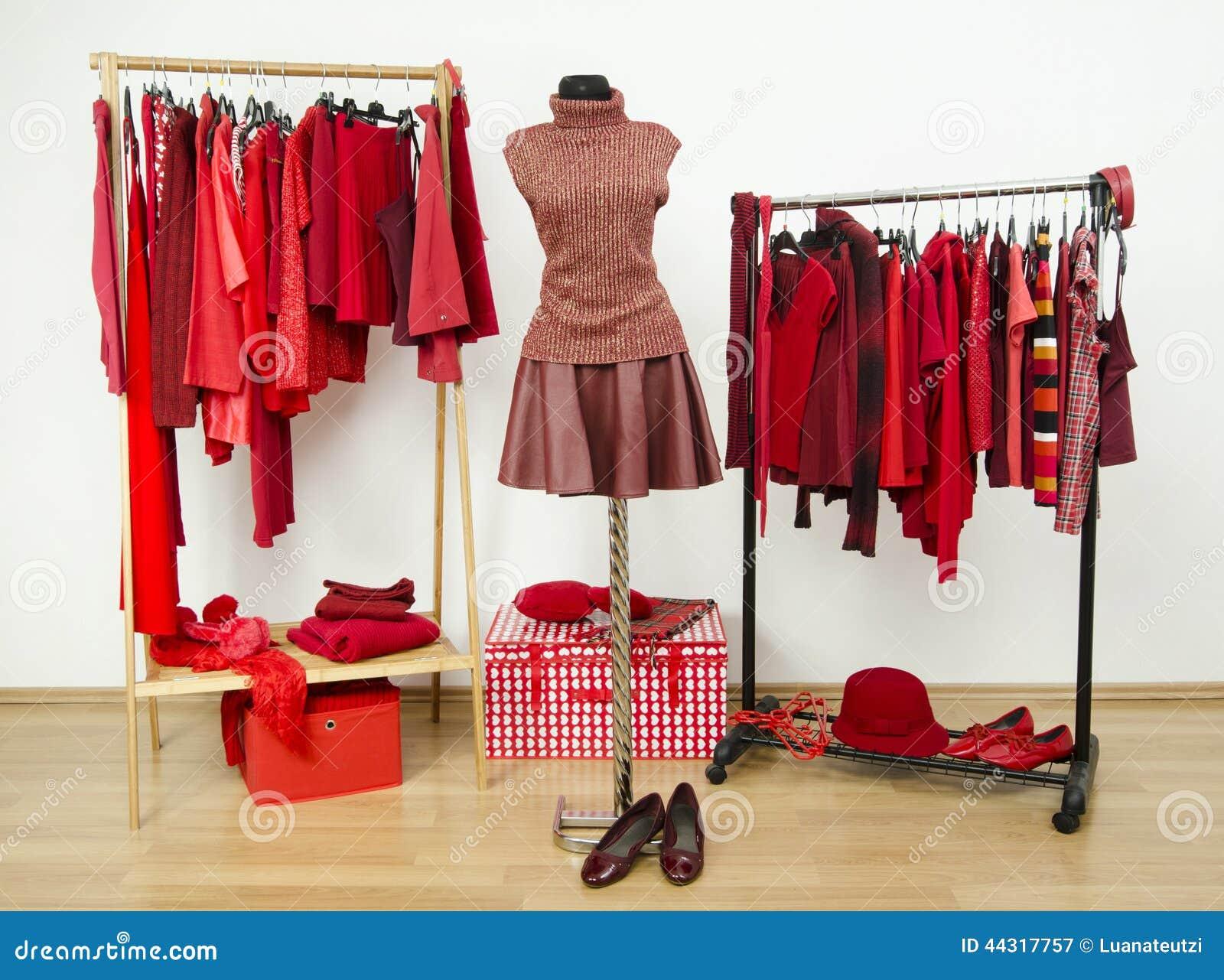 De garderobe met rode kleren schikte op hangers en een uitrusting op een ledenpop