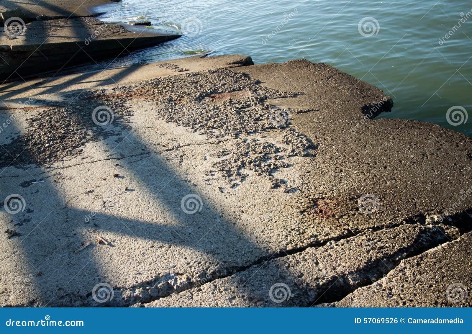 De geërodeerde samenvatting doorstond concrete plakken bij de rand van een vreedzame baai langs de Amerikaanse Noordwestenkustlij