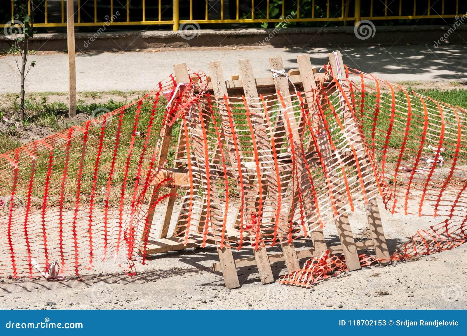 De geïmproviseerde barrière van de wegenbouwplaats met beschermende voorzichtigheids oranje omheining of netto om het werk van de