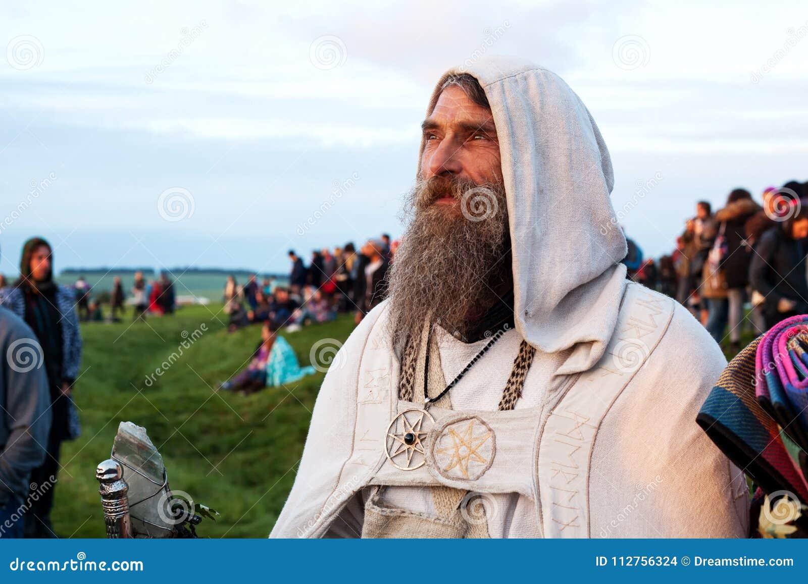 De gebaarde Druïde in robes let op de zonstijging in Stonehenge