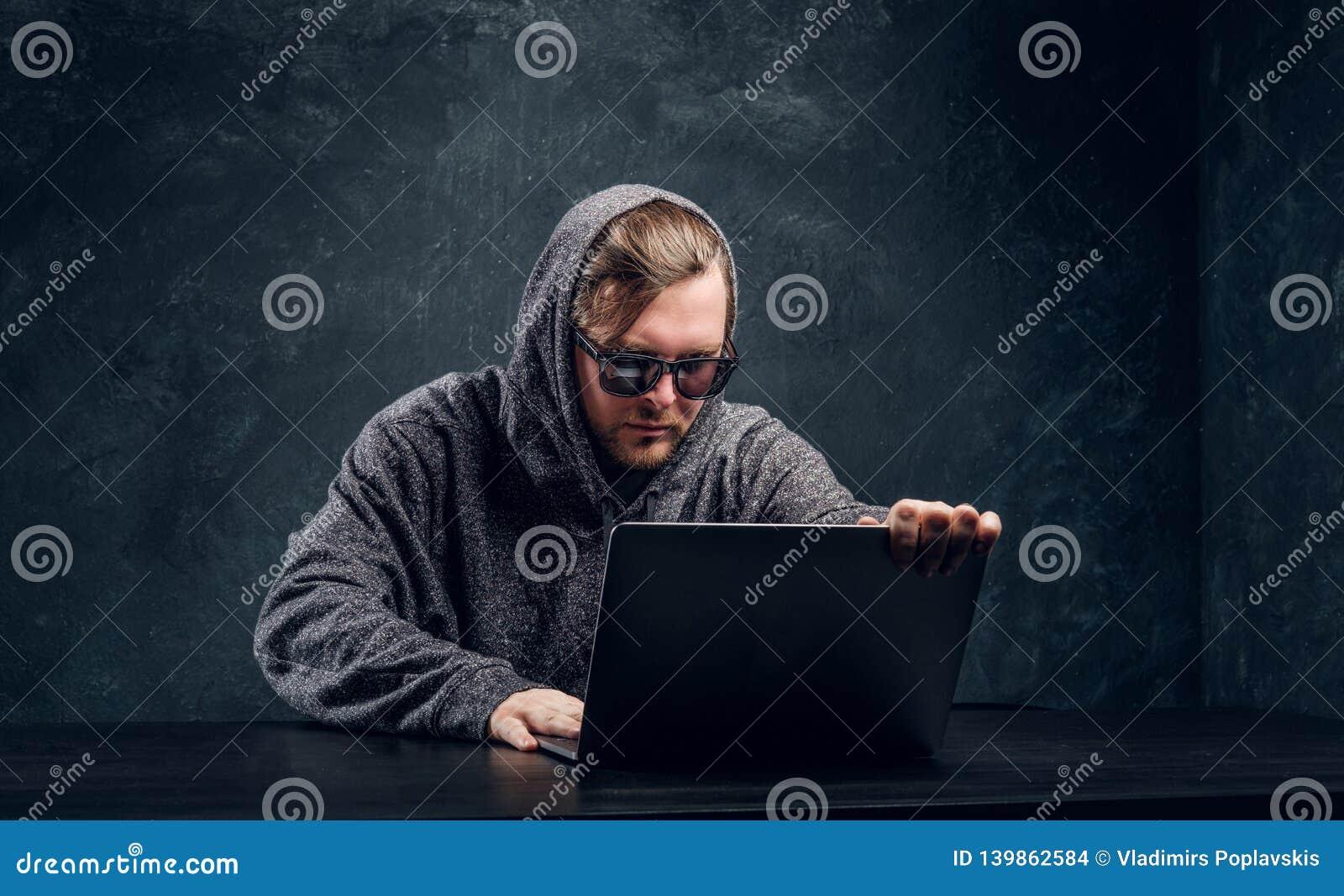 De gebaarde hakker in een grijze sweater en zonnebril zit bij de zwarte lijst
