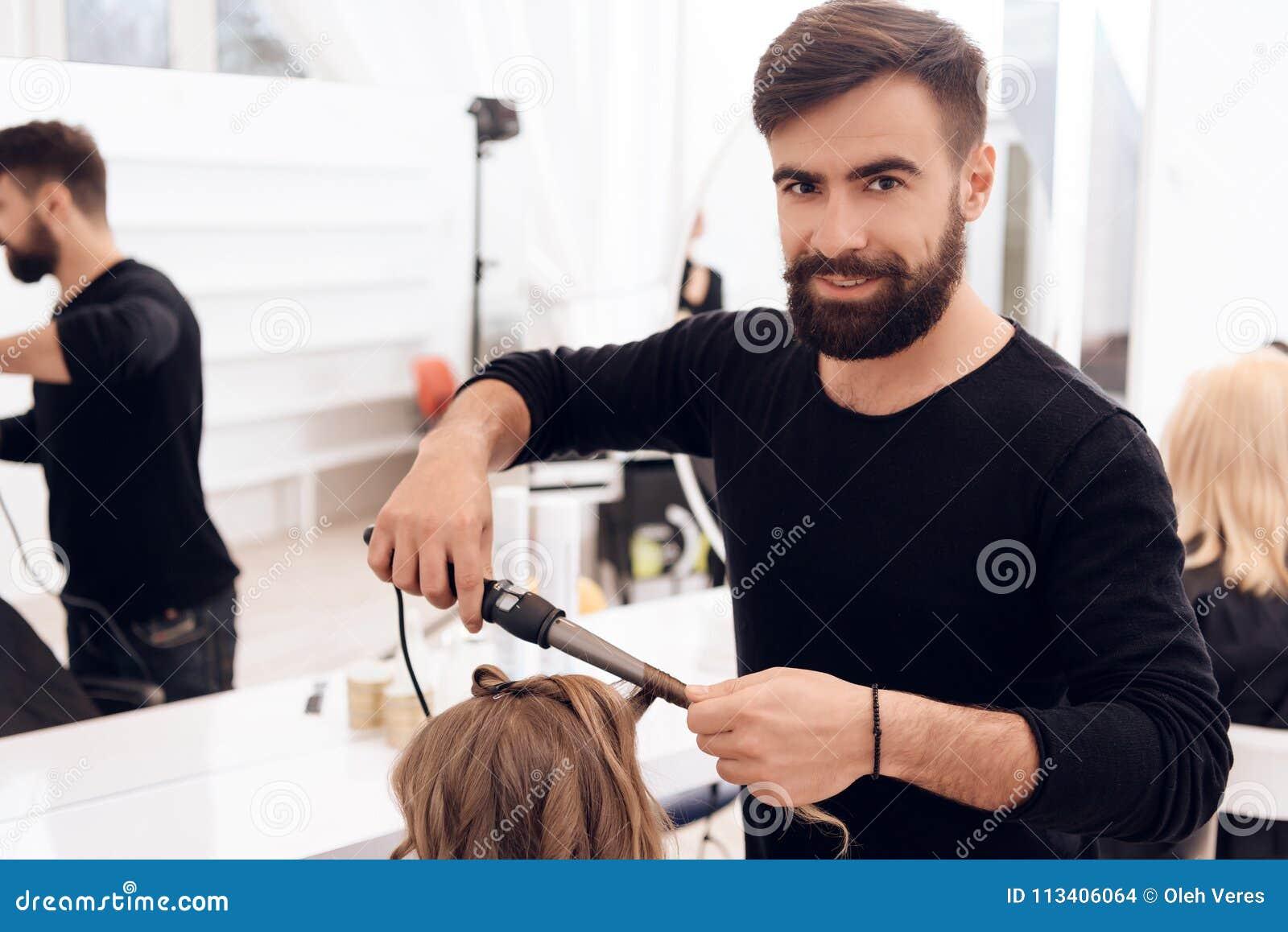 De gebaarde kapper maakt krullen op haar van mooi meisje met haarkrulspeld