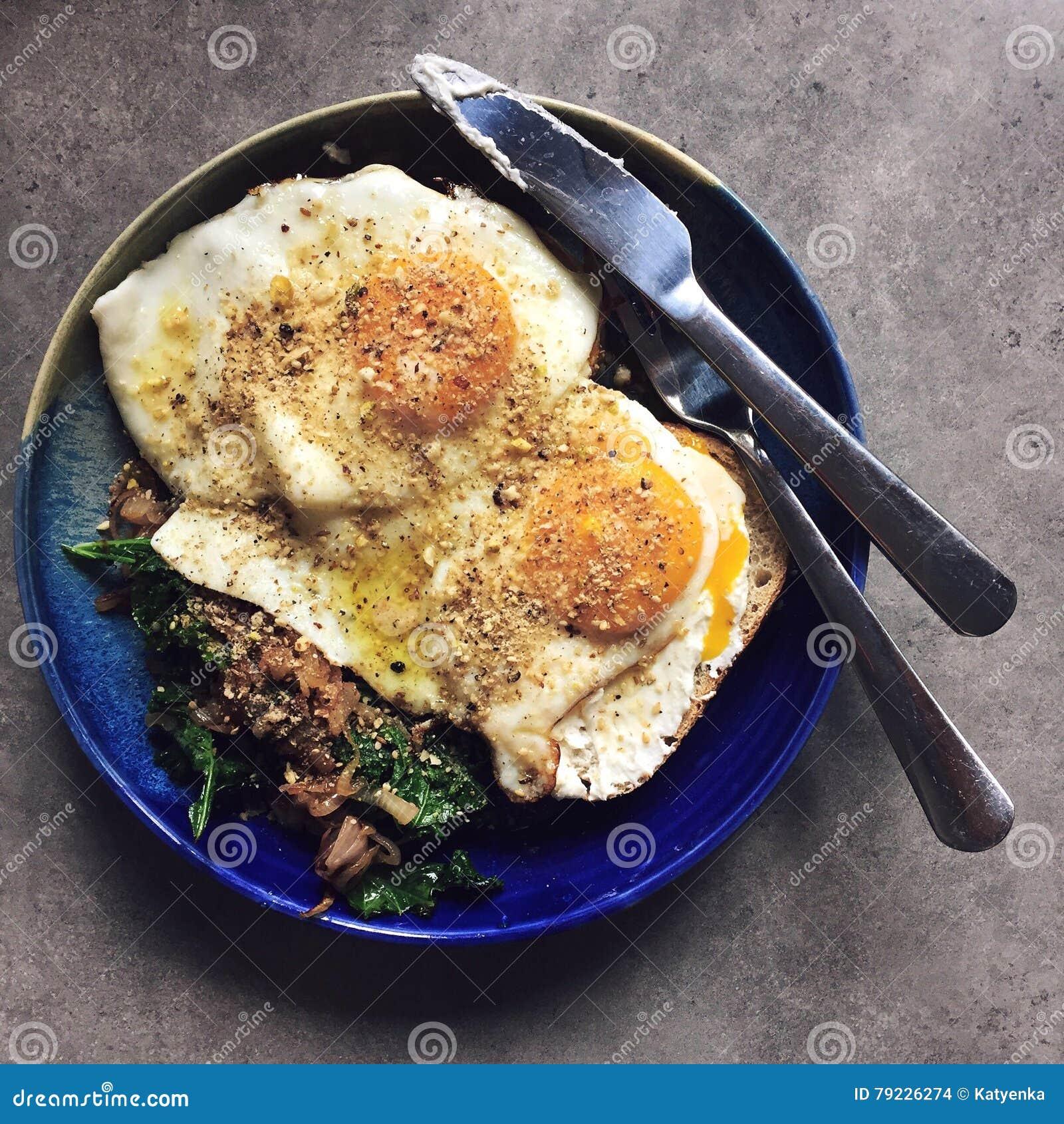 De gebraden eieren boven op van sautéed boerenkool en uien: eigengemaakt ontbijt