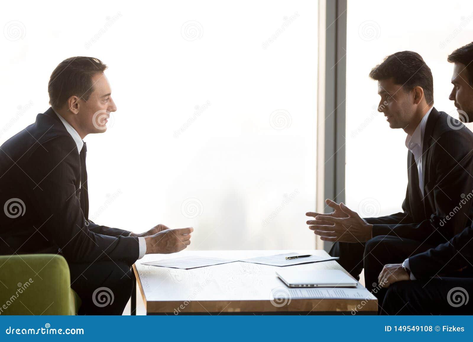 De geconcentreerde zakenlieden onderhandelen op vergadering die samenwerking bespreken