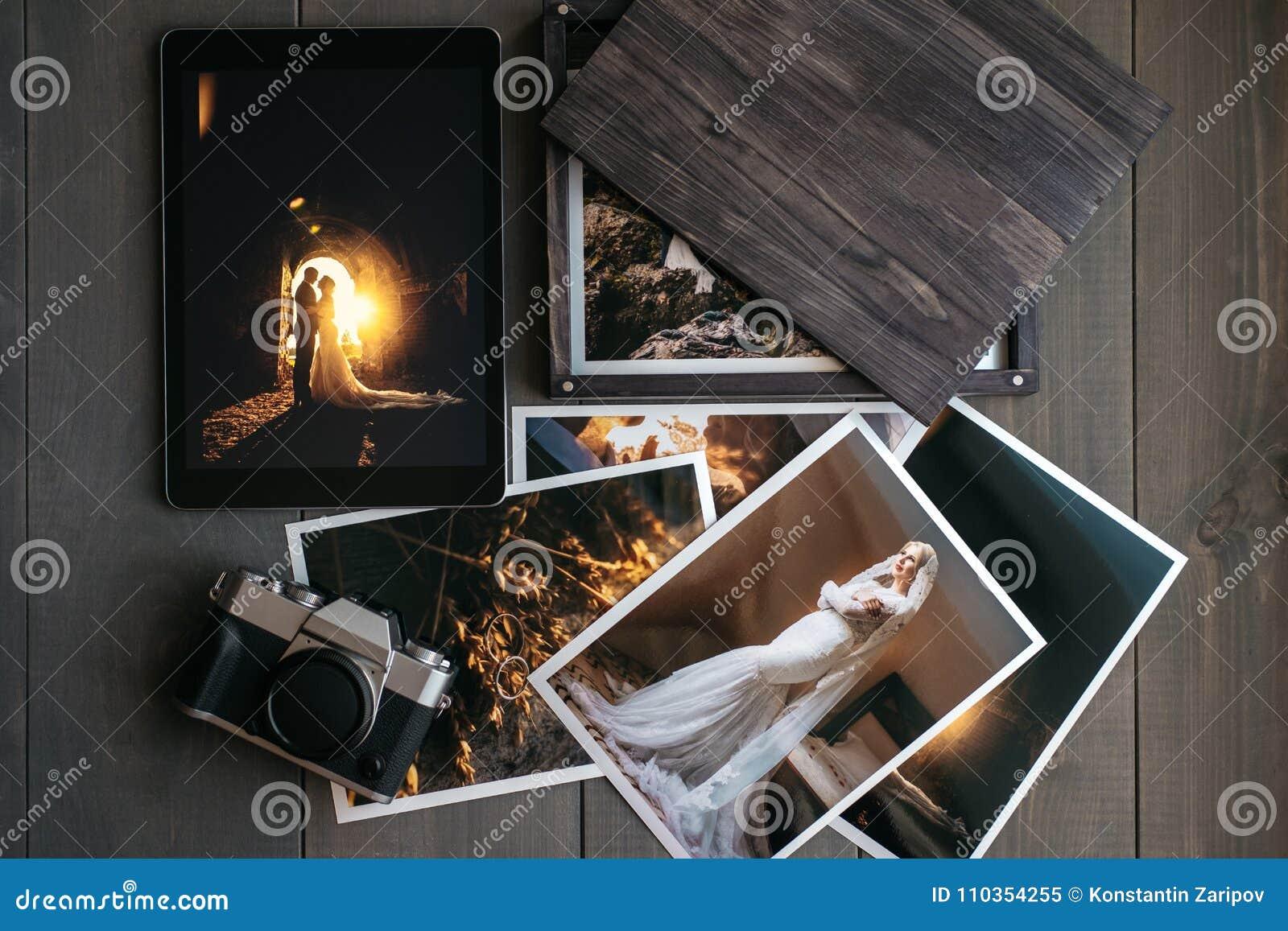 De gedrukte huwelijksfoto s, de houten doos, een uitstekende zwarte camera en een zwarte tablet met een beeld van een huwelijk ko