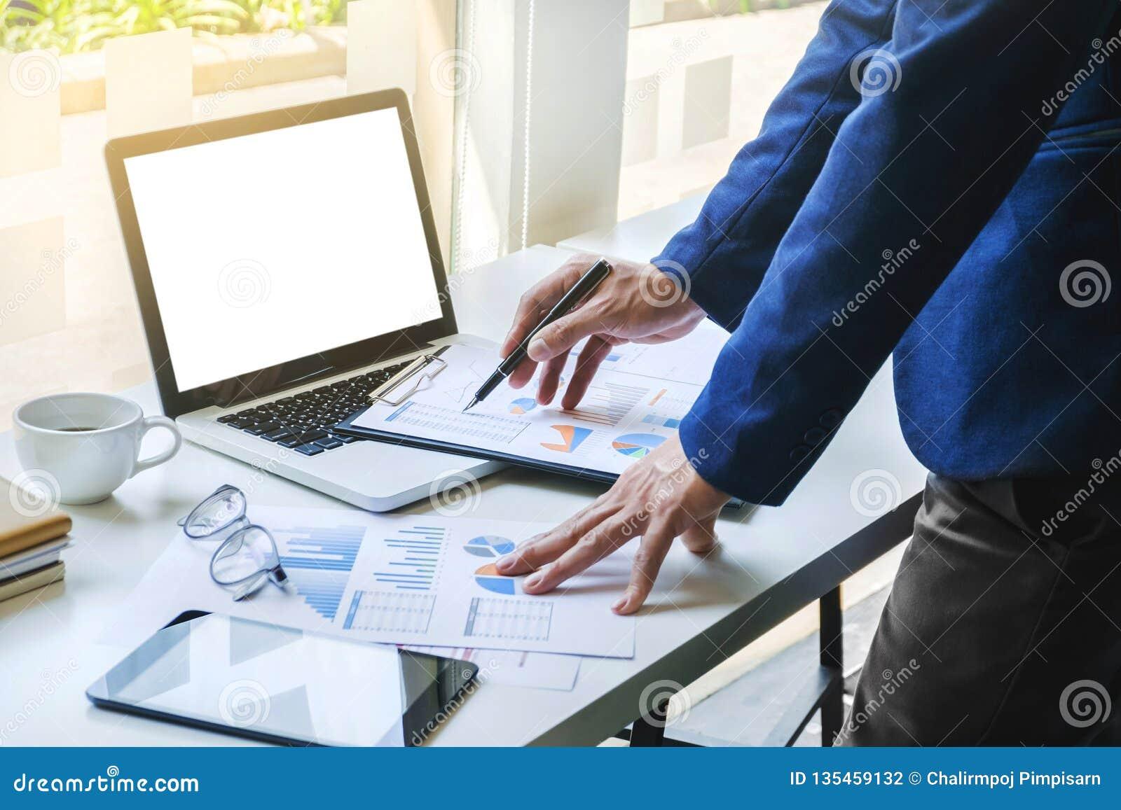 De gegevensdocumenten van de bedrijfsmensen werkende analyse van effectenbeursbedrijf op het kantoor met lege het schermlaptop