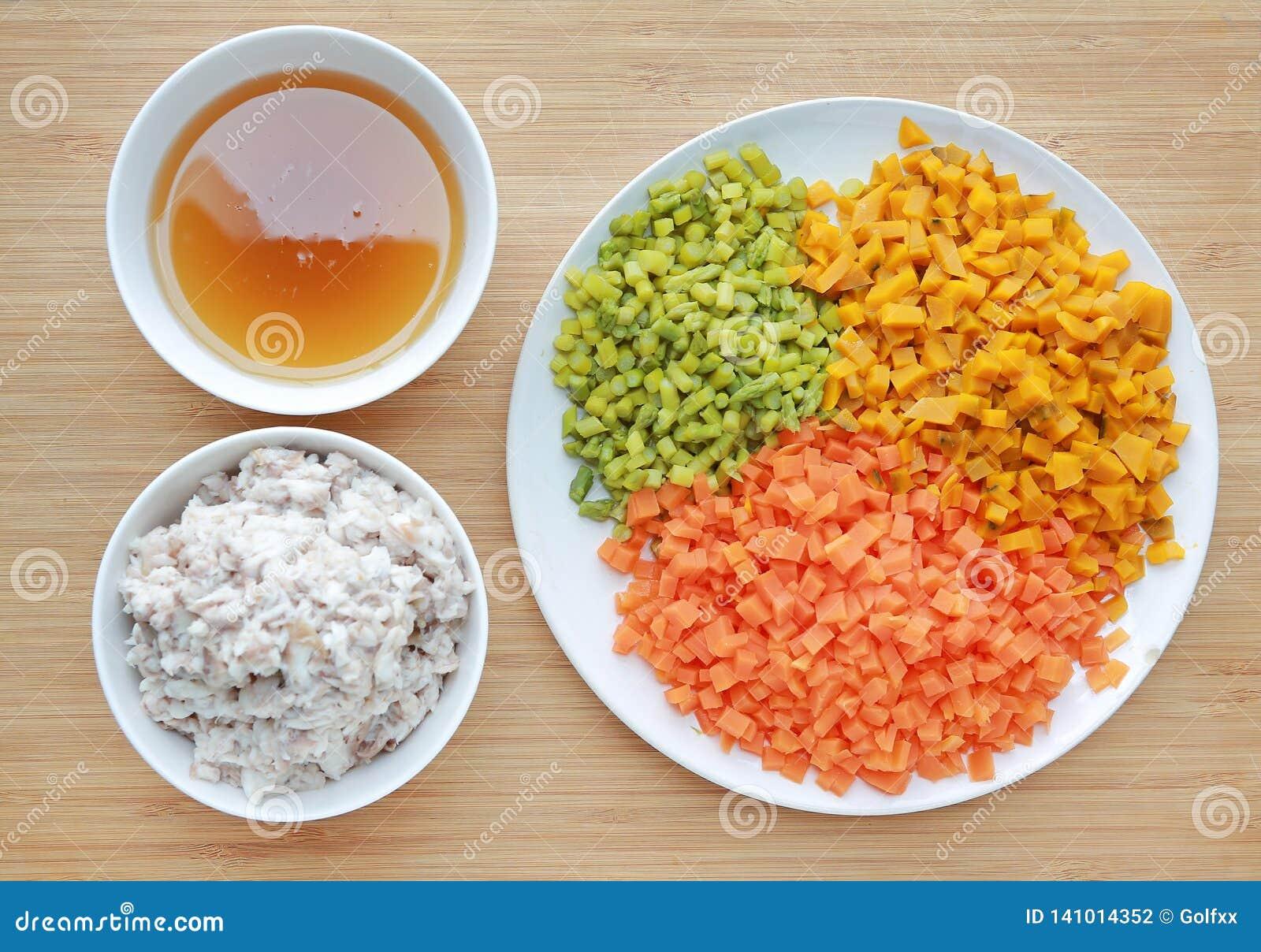 De gehakte groenten met soep en verbrijzeling vissen op witte plaat tegen houten raadsachtergrond