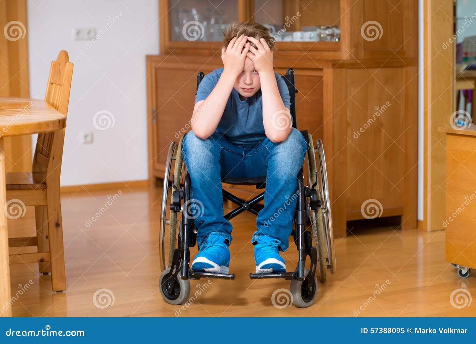 De gehandicapte jongen in rolstoel is droevig