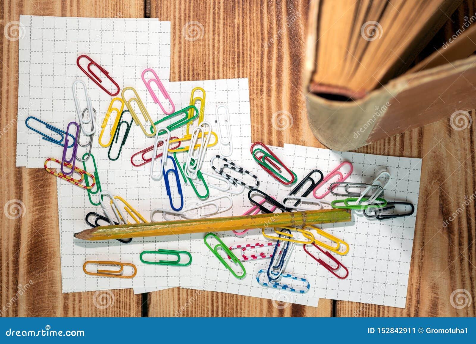 De gekleurde klemmen voor de etikettering van lusjes terwijl het bestuderen bij knoeien van verspreid op stukken van document voo