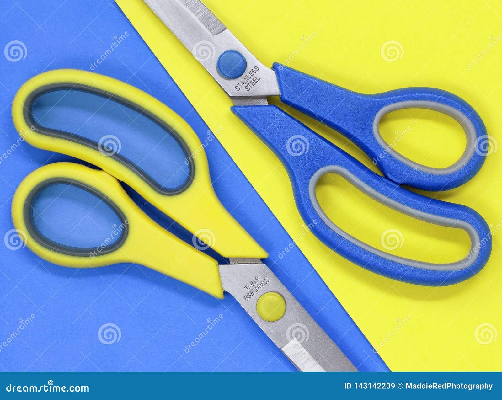 De gele en blauwe schaar, tegen het tegenover elkaar stellen legt vlak achtergrond