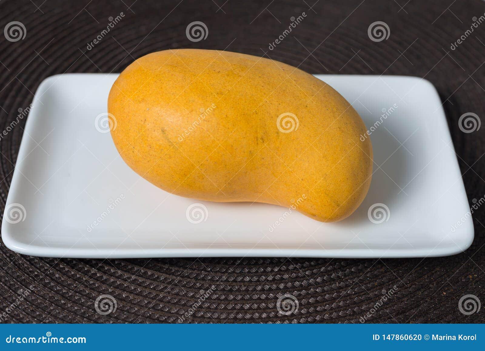 De gele rijpe mango op de witte plaat