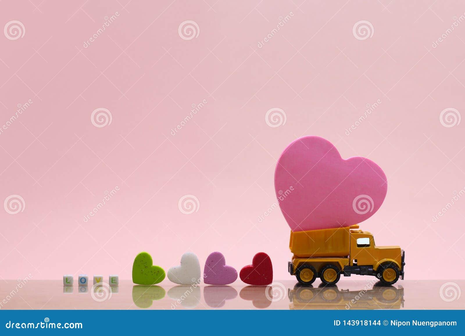 De gele stuk speelgoed vrachtwagen draagt roze hart op roze achtergrond
